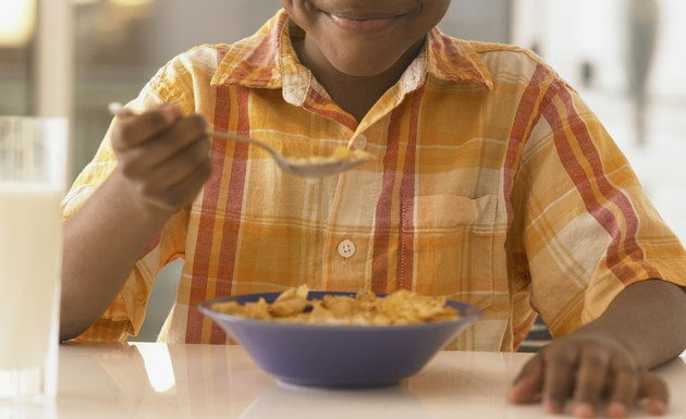 African boy eating cereal