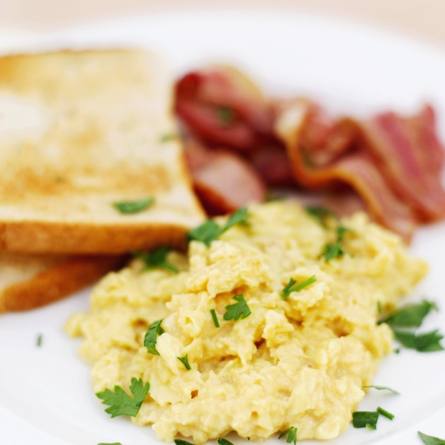 Close-up of scrambled eggs served with toast and bacon (blurred)
