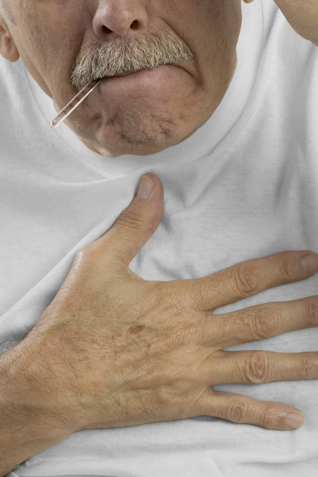 Senior man with hand on chest and thermometer in mouth