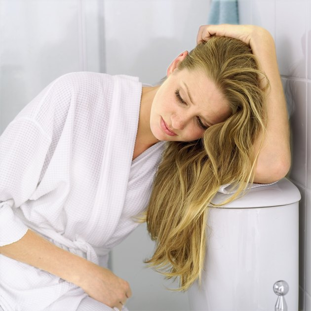 Young woman sitting on a toilet wearing a bathrobe