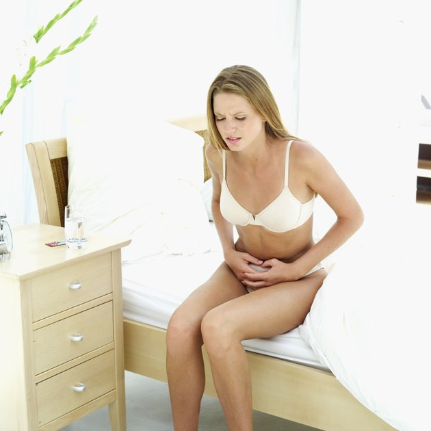 Young man sitting on a bed and holding her stomach in pain