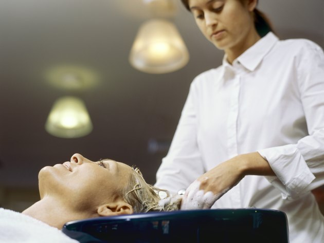 Low angle view of a hairdresser shampooing a young woman/s hair