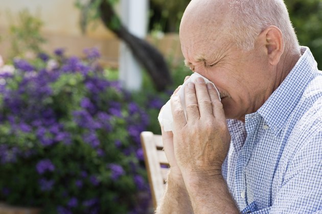 Man blowing nose outdoors