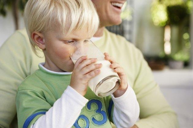 Boy in Fathers Lap Drinking Milk