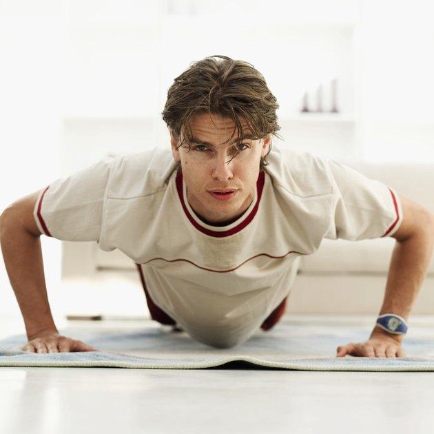 Close-up of a young man doing push ups on a mat