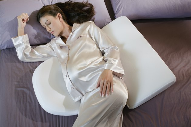 Pregnant woman sleeping with back and stomach pillows