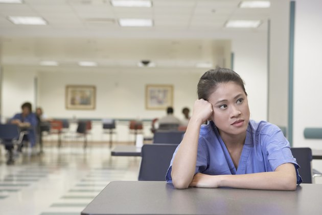Asian female doctor sitting at table leaning head on hand