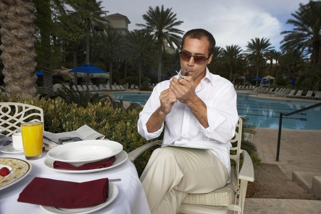 Man lighting cigarette by swimming pool
