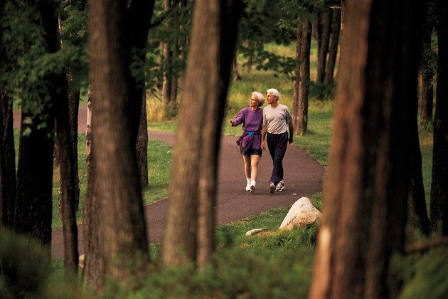 Mature couple walking on trail through forest