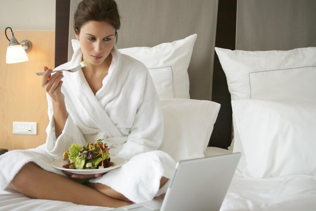 Woman wearing robe eating salad in bed with laptop