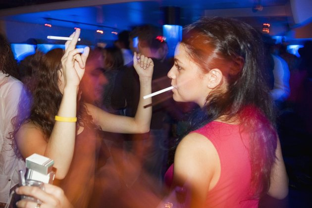 Close-up of two women smoking and dancing in nightclub, with people in the background