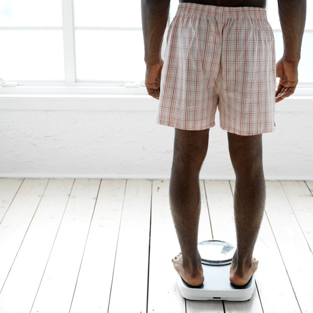 behind of a young man weighing himself on a scale