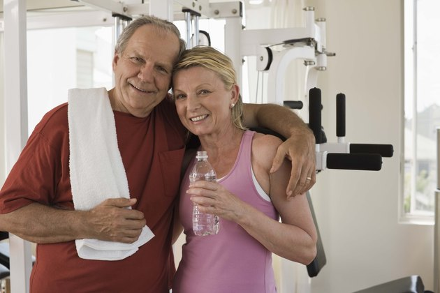 Smiling couple embracing in home gym