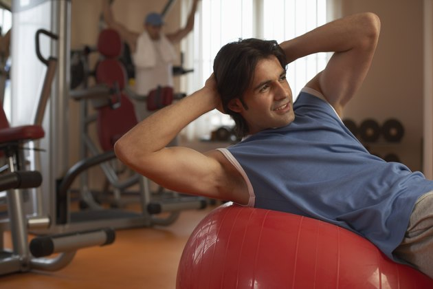 Man exercising on exercise ball in gym