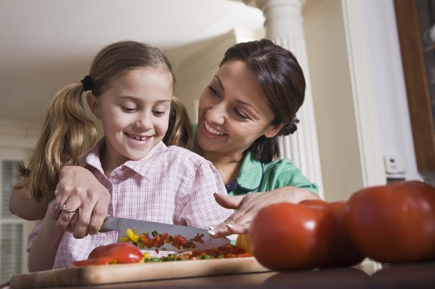 Mother teaching daughter to chop vegetables