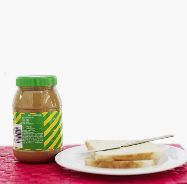 A jar of peanut butter next to a plate with bread and a butter knife