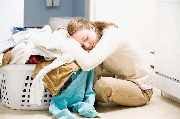 Overwhelmed woman with basket of laundry on floor