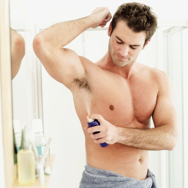 young man spraying deodorant