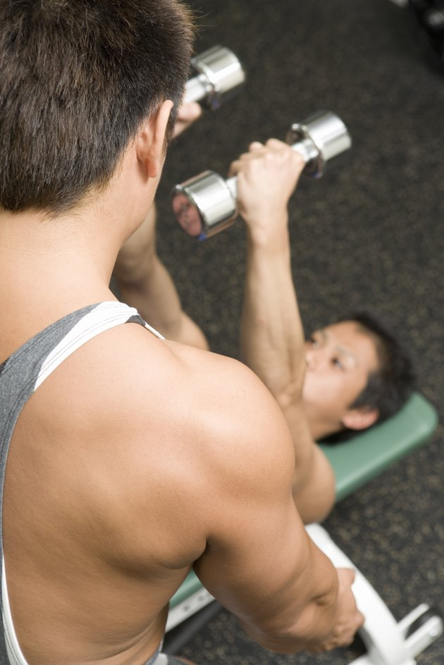 Men exercising in gym, one man lifting dumbbell, high angle view, differential focus