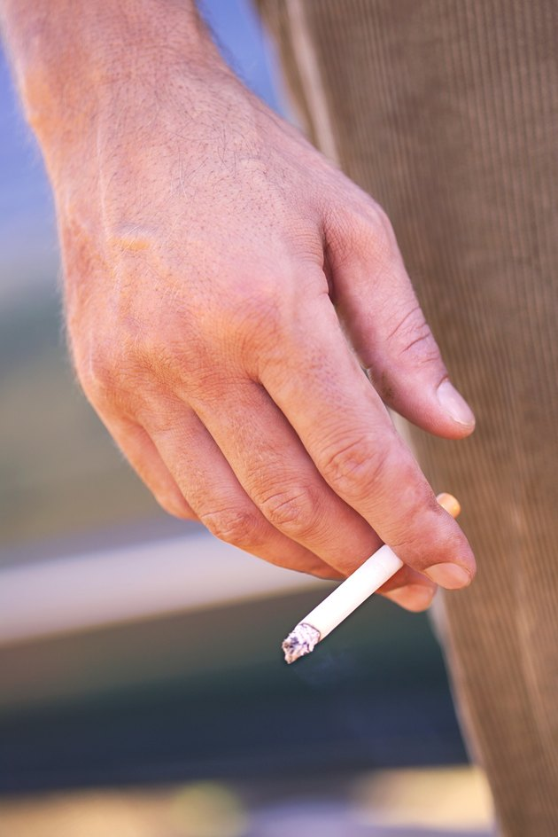 Close-up of a man's hand holding a cigarette at his side.