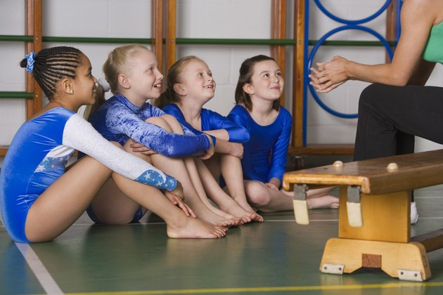 Coach talking to gymnastics girls team