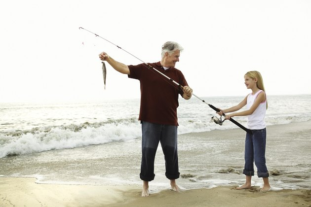 Father and daughter fishing on beach