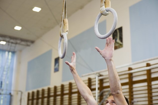 Male gymnast reaching for rings