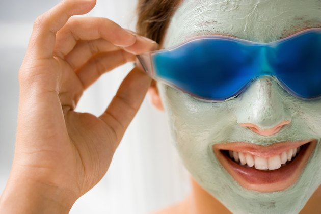Smiling woman with facial mask and gel eyemask