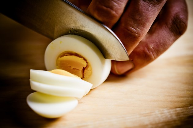 Close-up of cook slicing hard-boiled egg