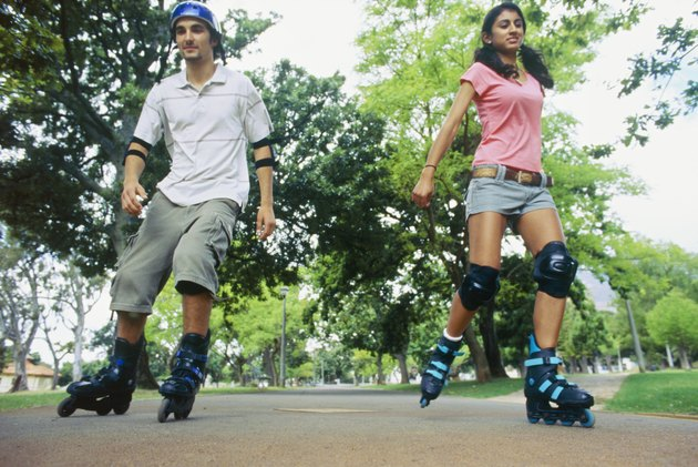 Low angle view of a young couple  inline skating in a park