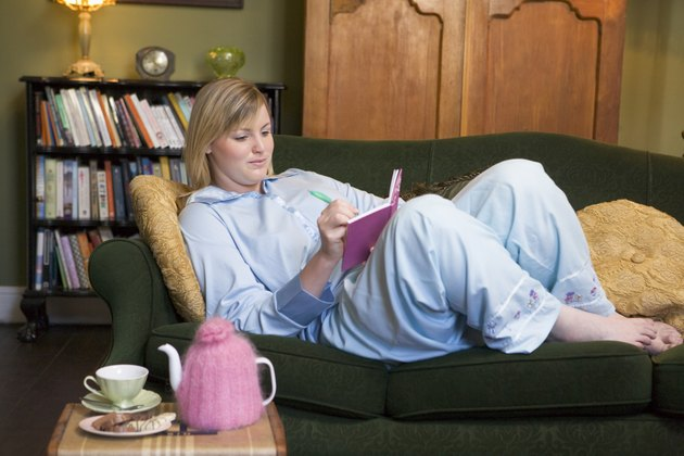Young woman lying on sofa at home writing in her diary