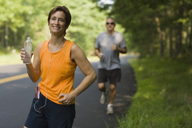 Smiling jogger with bottle of water