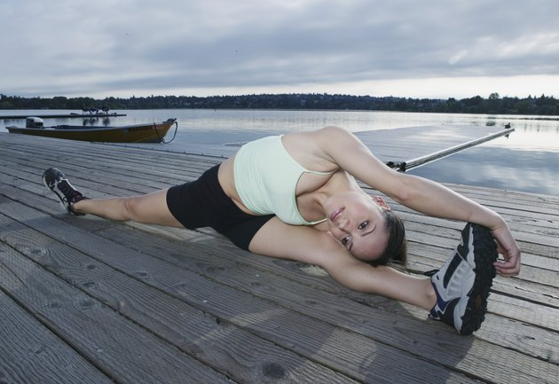 Young woman exercising on dock at lake