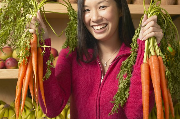Portrait of a young woman smiling holding vegetables
