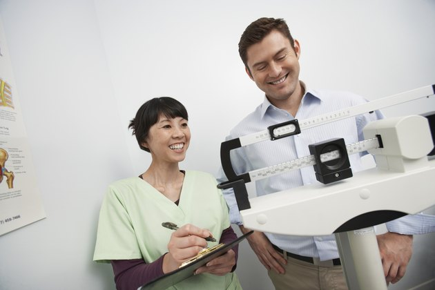 Man standing on weighing scales beside nurse in hospital