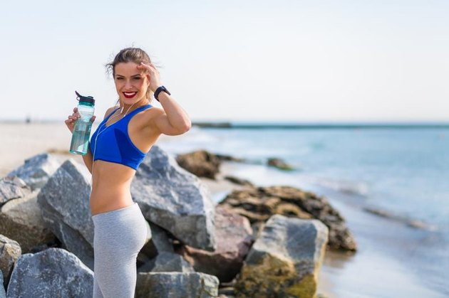 Woman working out outdoors in the summer at the beachWoman working out outdoors in the summer at the beach