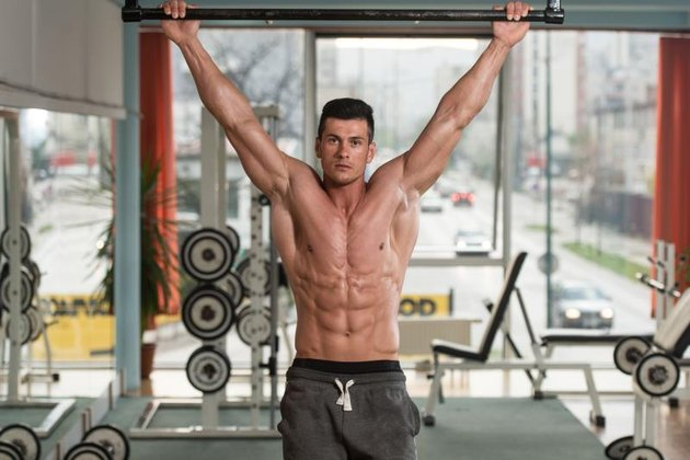 Young Male Athlete Doing Pull Ups - Chin-Ups In The Gym