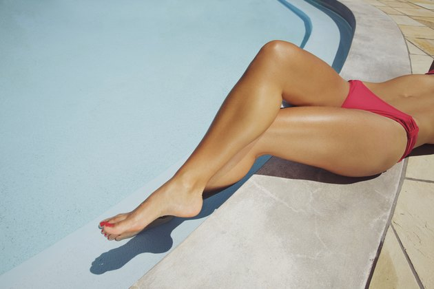 Young lady relaxing by swimming pool