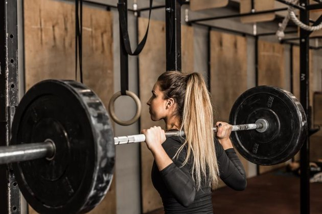 Closeup young and fit female athlete performed squats in the gym.Beautiful blonde girl during workout in gym with barbell on her shoulders.