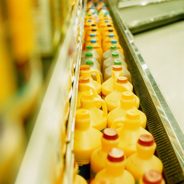 Rows of plastic containers of orange juice in supermarket