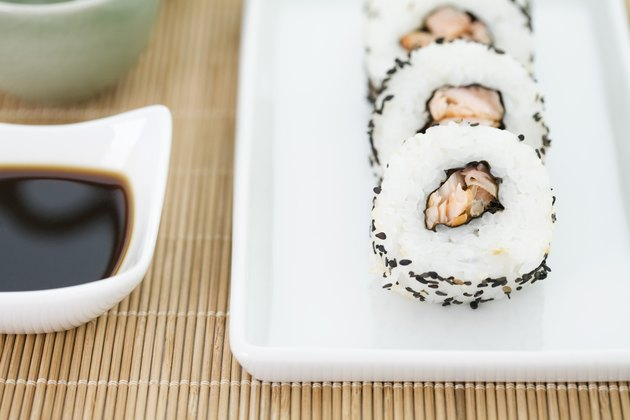 Cropped view of pieces of sushi with soy sauce, close-up