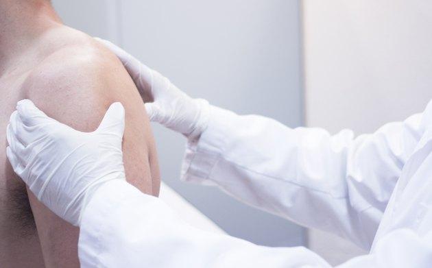 Dooctor surgeon examines patient shoulder arm injury