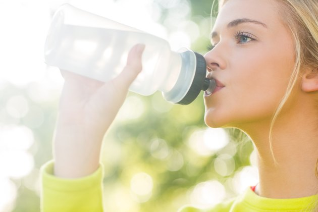 Fit blonde drinking from sports bottle
