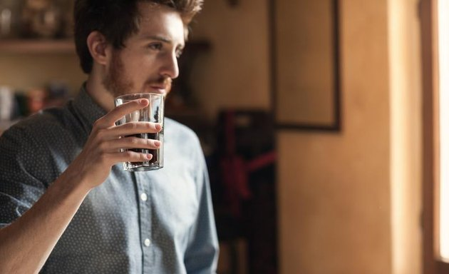 Hipster young man drinking a glass of coke and looking away next to a window