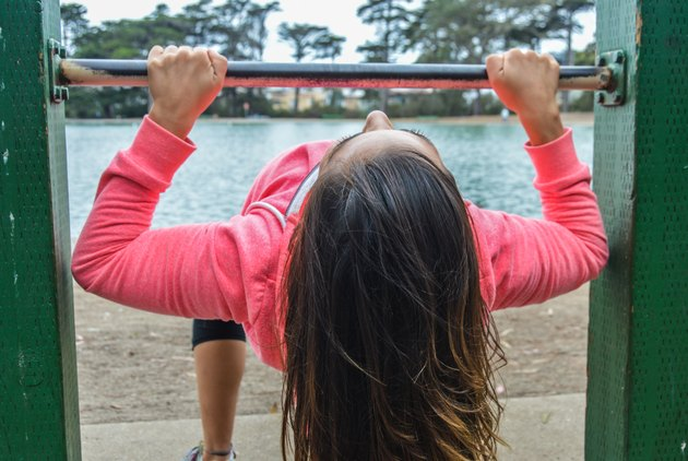 Athletic skinny woman doing pull up rows