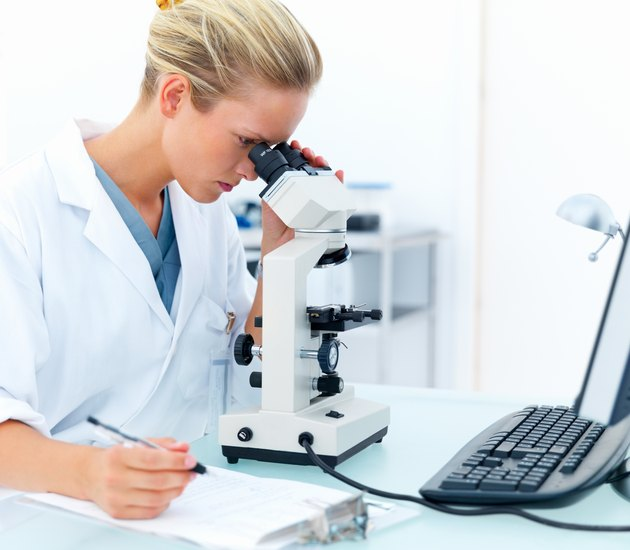 Female researcher looking into a microscope and writing notes