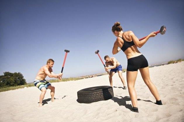 Three strong athletes doing hammer strike on a truck tire during gym exercise outside on beach. Muscular active people in 20s training to maintain healthy lifestyle.