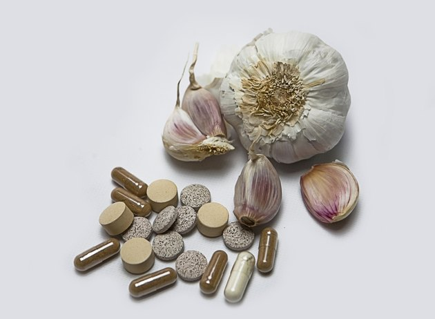 Garlic and herbal supplement pills, alternative medicine concept