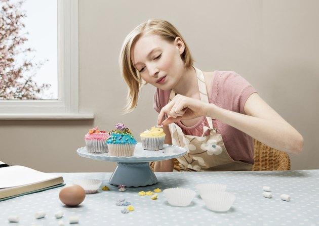 woman decorating cupcakes.