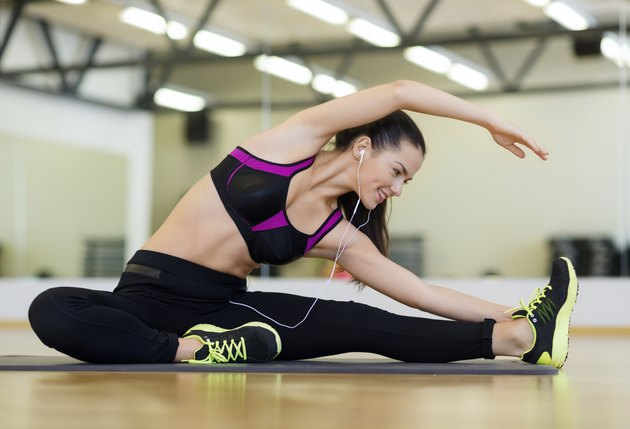 stretching young woman with earphones in the gym